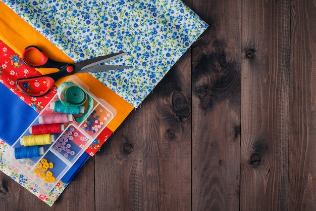Forbici, rocchetti di filo e aghi, tessuto a strisce