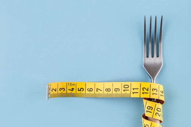 Forcella con un nastro di misurazione, una dieta o un concetto di cibo sano