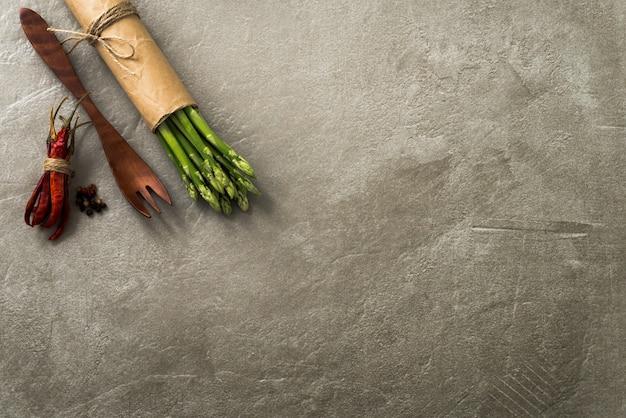 Forcella del peperoncino rosso e di legno dello spazio con il fondo degli asparagi