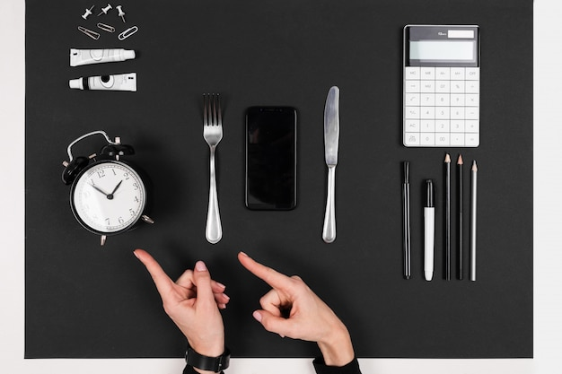 Forchetta, coltello, computer portatile, calcolatrice, penne, matite, carta, sveglia isolata sul nero