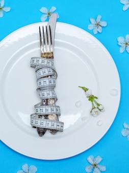 Forchetta con un coltello avvolto in un nastro di misurazione si trovano su un piatto di ceramica rotondo bianco