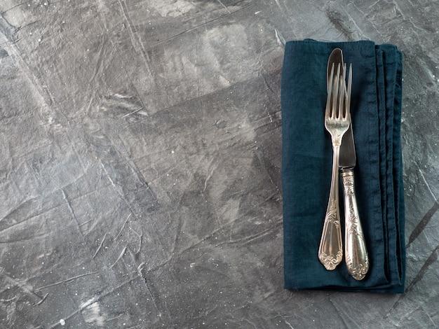 Forchetta e coltello d'argento sul tovagliolo di tela verde smeraldo verde scuro sopra struttura grigia