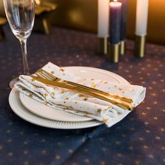 Forchetta e coltello d'oro sul piatto bianco