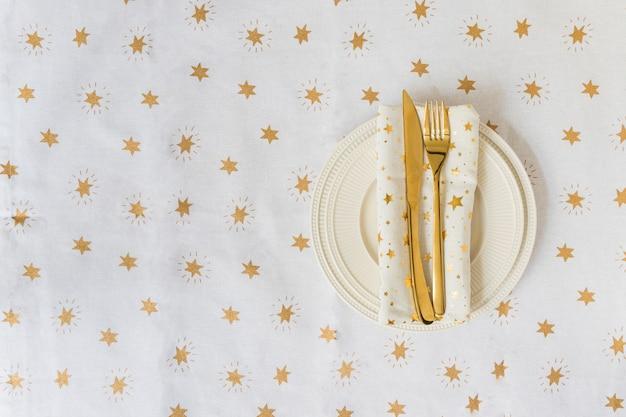 Forchetta e coltello d'oro sul piatto leggero