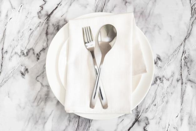 Forchetta e cucchiaio con un tovagliolo sul piatto sulla superficie del marmo