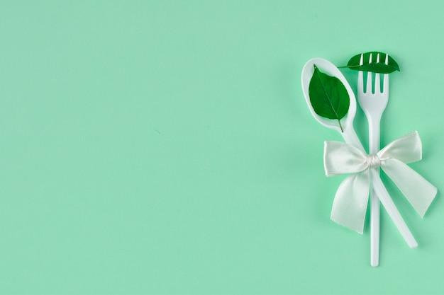 Forchetta e cucchiaio di plastica bianca con fiocco