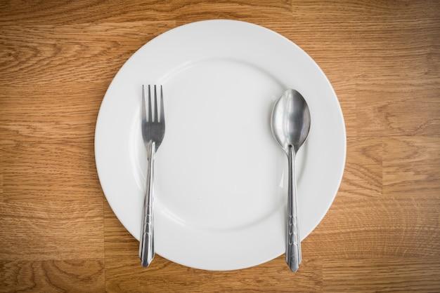 Forchetta e cucchiaio e piatto bianco vuoto