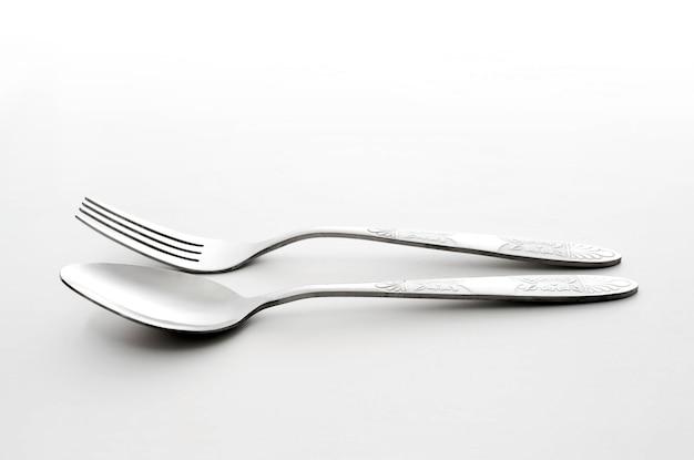 Forchetta e cucchiaio su sfondo bianco