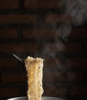 Forchetta per spaghetti istantanei caldi in pentola. tagliatella al vapore