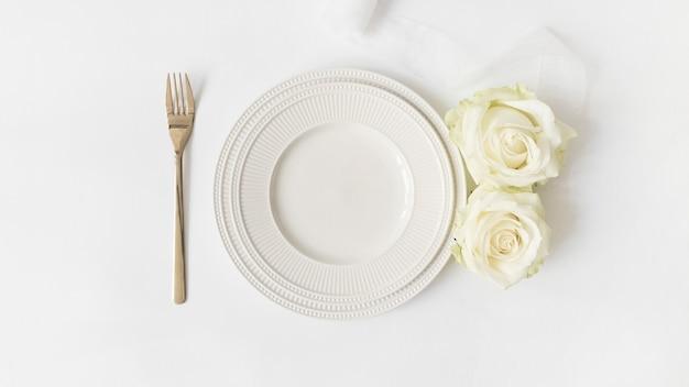 Forchetta; piatto di ceramica; rose e nastro di raso su sfondo bianco