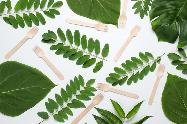 Forchette di legno tra il verde delle foglie tropicali su sfondo bianco. sfondo eco creativo