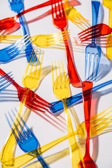 Forchette di plastica colorate su sfondo bianco