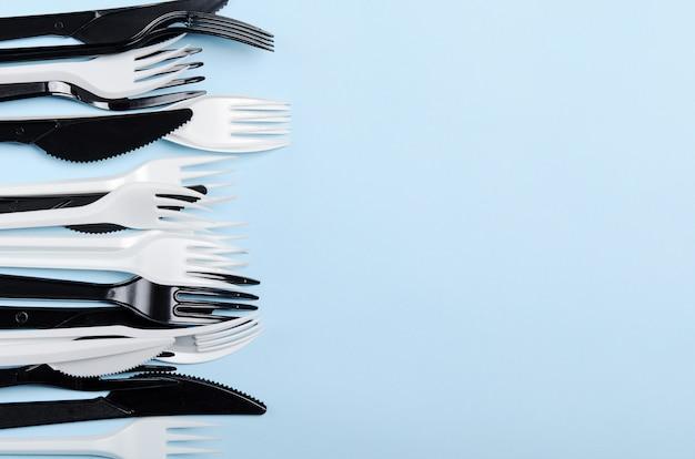 Forchette e coltelli eliminabili bianchi e neri di plastica su un fondo blu. piatti di plastica. copia spazio, vista dall'alto, disteso.