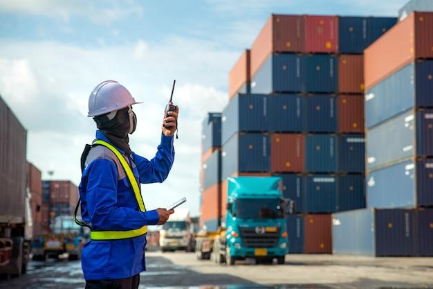 Foreman usa e parla walkie-talkie per controllare il caricamento di container box su camion presso la stazione di deposito container per l'importazione logistica import export