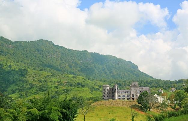 Foresta di montagne con castello in costruzione.