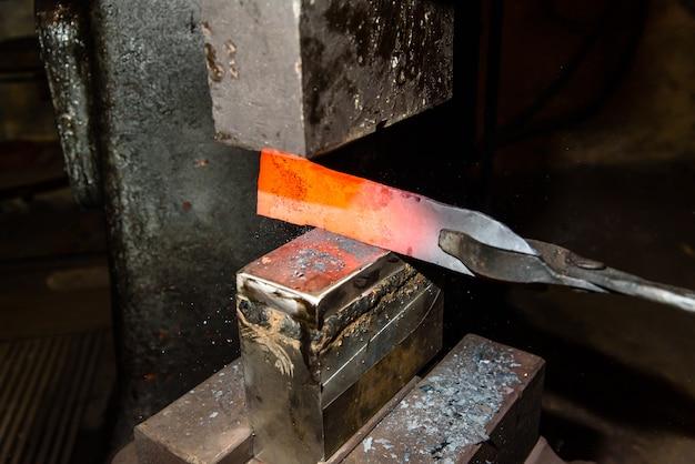 Forgia il metallo fuso. fare coltelli