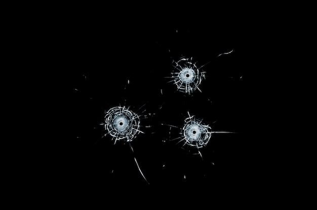 Fori di pallottola tripla di vetro rotto in vetro isolato sul nero
