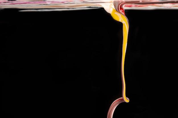Forma acrilica colorata in acqua su sfondo nero