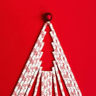 Forma creativa dell'albero di natale dalle cannucce e dalla palla del nuovo anno su fondo rosso. concetto di vacanza invernale con colori vivaci. disteso.