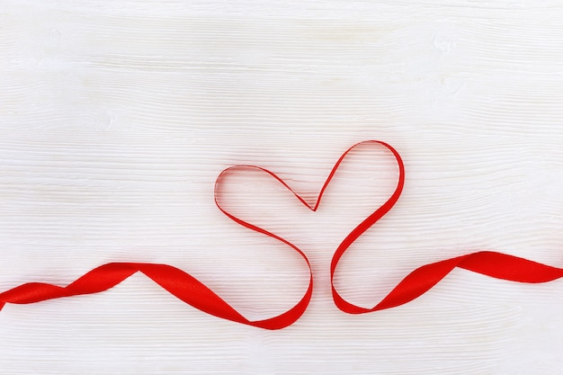 Forma del cuore dal nastro rosso su legno bianco
