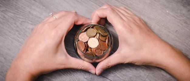 Forma del cuore della mano che tiene monete