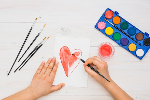 Forma del cuore della pittura della mano della persona con il colpo rosso della spazzola di colore di acqua sopra la tavola di legno