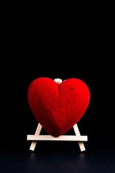 Forma del cuore di concetto di san valentino sul supporto di legno su fondo nero