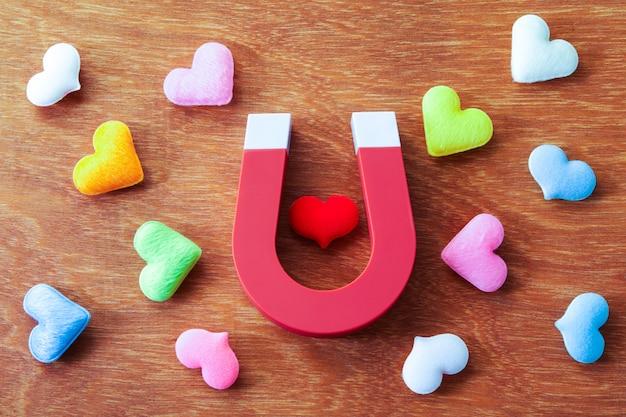 Forma del cuore di gravita del magnete su fondo di legno, concetto di amore