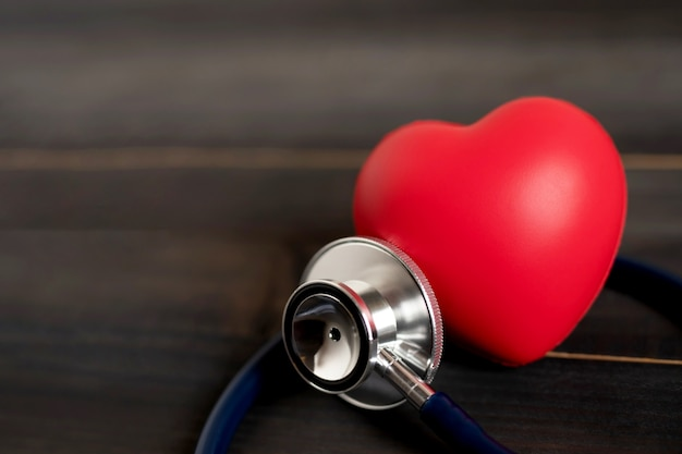 Forma di amore del cuore rosso e stetoscopio dei medici sulla tavola di legno, controllo dell'ipertensione o concetto di assicurazione sulla vita dell'ospedale,