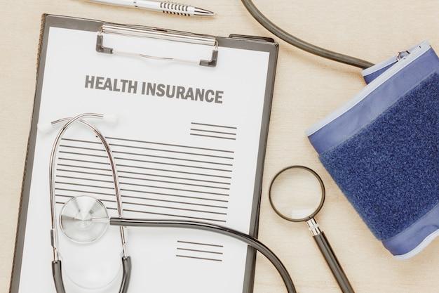 Forma di assicurazione sanitaria superiore e manometro con stetoscopio su sfondo in legno.document o applicazione su clip board.flat lay e copy space.medical e concetto di assicurazione.