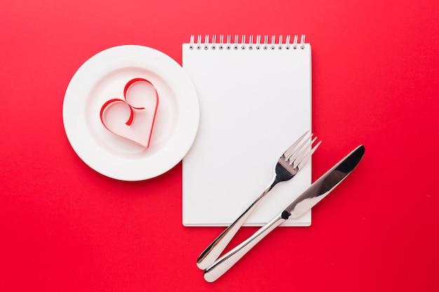 Forma di carta del cuore sul piatto con il taccuino per il giorno di biglietti di s. valentino