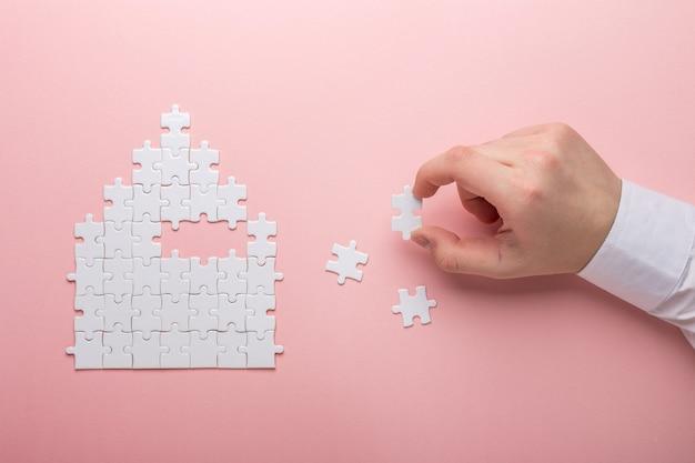 Forma di casa puzzle il concetto di affitto, mutuo mano che tiene pezzo di puzzle bianco