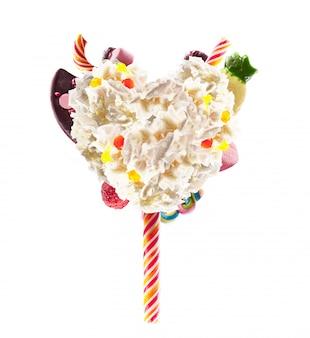 Forma di cuore da panna montata con dolci, gelatine, vista frontale del cuore. tendenza alimentare pazza di freakshake. cuore di crema, pieno di bacche e gelatina di caramelle, caramelle al cioccolato concetto isolato su bianco.