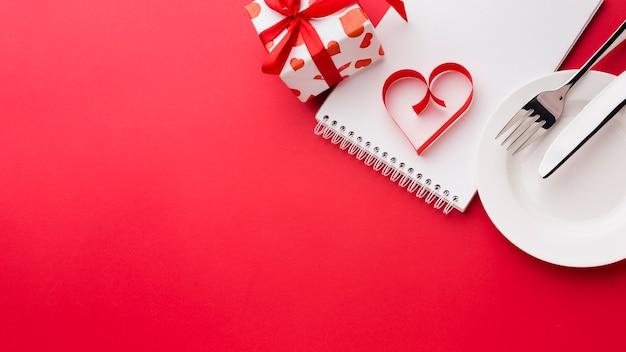 Forma di cuore di carta sul taccuino con il piatto e presente per il giorno di biglietti di s. valentino