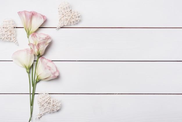 Forma di cuore fatto a mano con fiori rosa eustoma sullo scrittorio di legno bianco