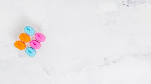 Forma di gelo popsicle multicolore su una superficie grigia