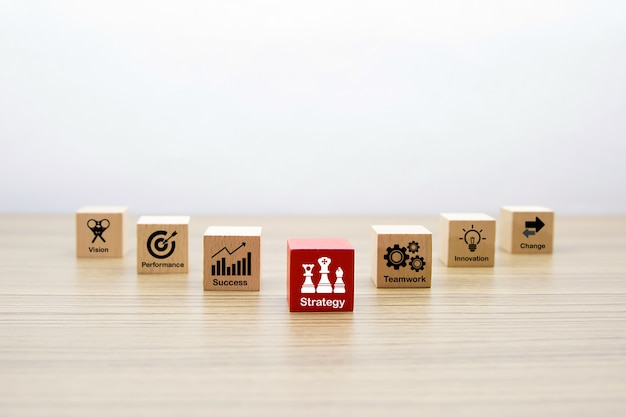 Forma di legno del cubo con le icone di affari per il concetto di successo e di strategia.