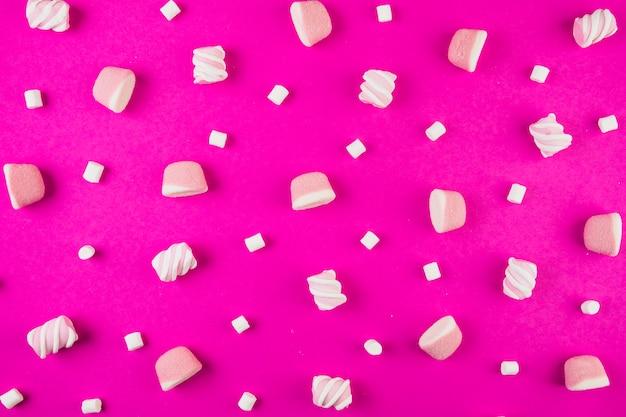 Forma diversa di marshmallow su sfondo rosa