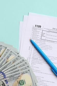 Forma fiscale si trova vicino a centinaia di banconote da un dollaro e penna blu su