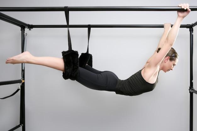 Forma fisica dell'istruttore di ginnastica della donna di sport dei pilates del cadillac