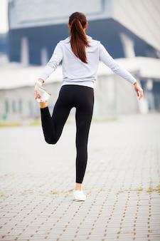 Forma fisica, donna che fa allungando esercizio sullo stadio