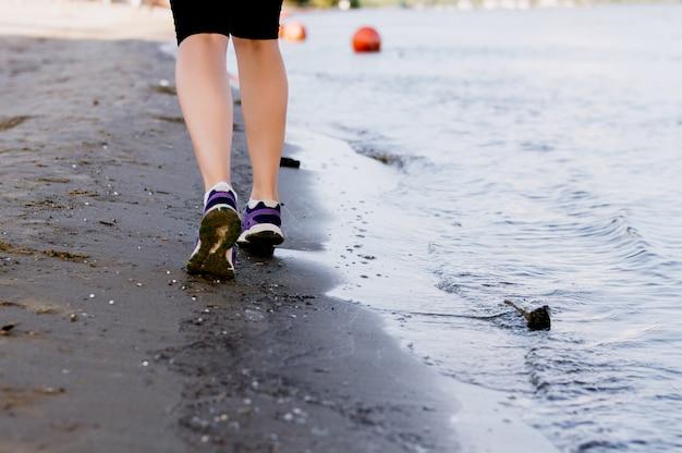 Forma fisica e funzionamento sulla spiaggia, gambe del corridore della donna in scarpe sulla sabbia vicino al mare