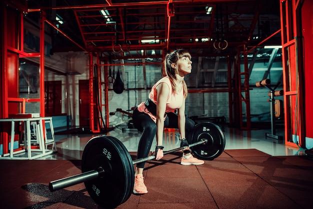 Forma fisica femminile che esegue facendo esercizio deadlift con la barra del peso