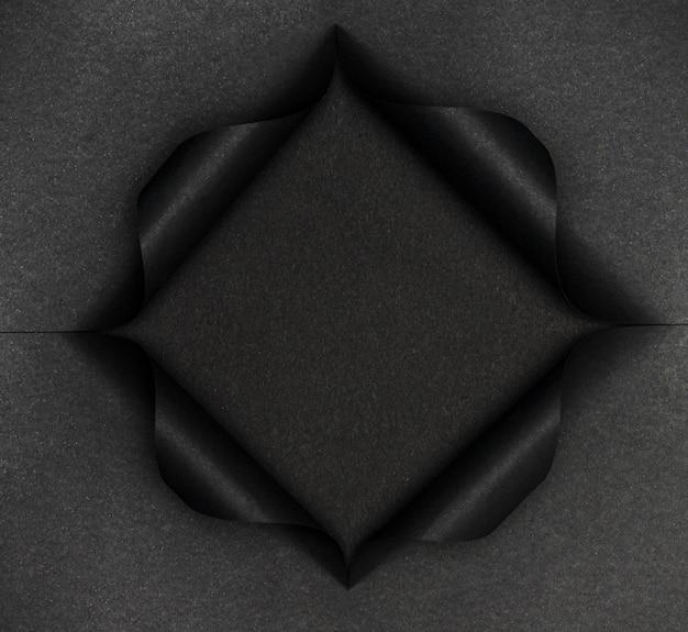Forma nera astratta su carta nera strappata