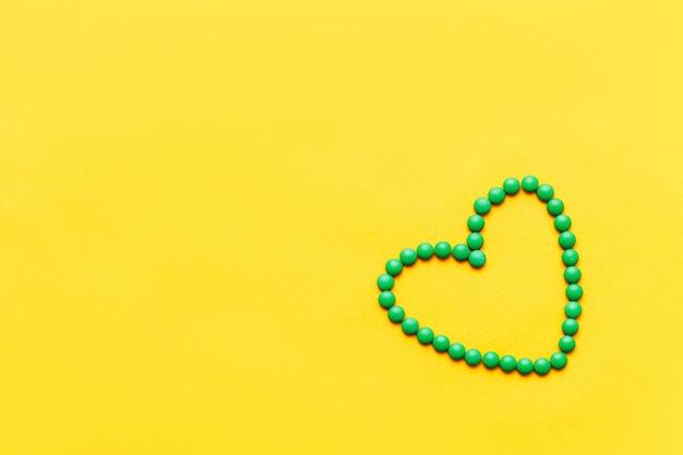 Forma rotonda verde del cuore delle compresse delle pillole su fondo yuellow