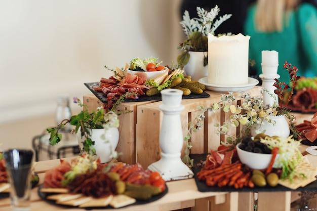 Formaggi affettati e carne serviti su piastra con olivas stand su scatole di legno