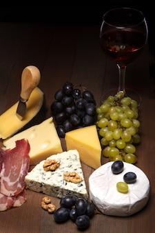 Formaggi assortiti, noci, uva, frutta, carne affumicata e un bicchiere di vino su un tavolo da portata. stile scuro e lunatico.
