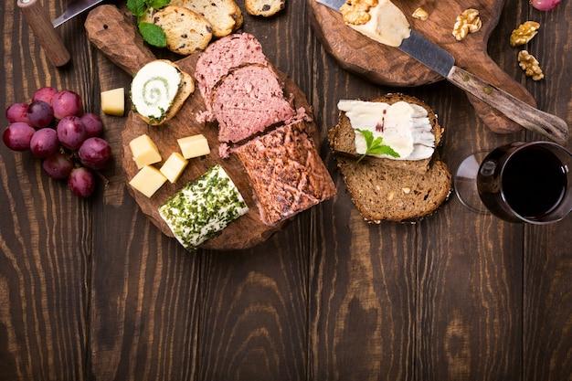 Formaggi assortiti su piatto di assi di legno, uva, vino da pane e patè