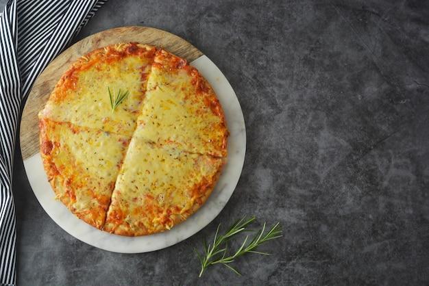 Formaggi deliziosa pizza fatta in casa con crosta spessa sul tavolo scuro