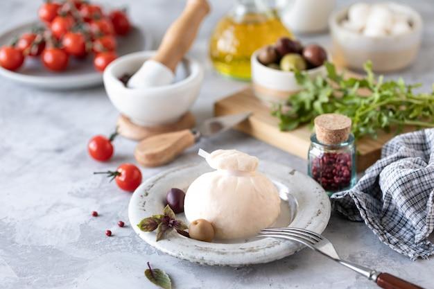 Formaggi italiani burrata e mozzarella con olive, pomodorini e rucola su un piatto rotondo bianco su sfondo chiaro